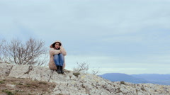 Lonely meditative girl on the top of a windy hill - stock footage