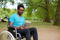 Stock Photo of young indian man in a wheelchair using a tablet computer