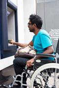 Disabled man withdrawing cash at the atm Stock Photos