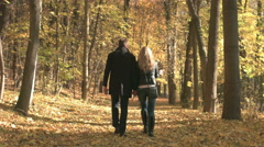 Young couple enjoying the fall season, walking in the fallen leafs - stock footage