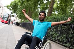 disabled man in a wheelchair celebrating - stock photo