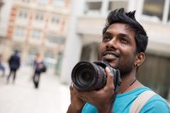 Young indian man on holiday taking photos Stock Photos