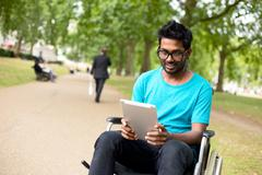 Disabled man in the park with a tablet computer Stock Photos