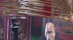Young woman burns incense, Hong Kong temple Stock Footage