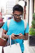 young indian man using his phone and holding shopping bags - stock photo