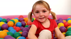 Smiling girl inside a ball pit Stock Footage