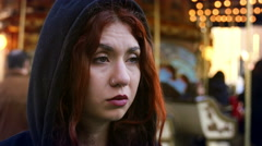 Confused girl in front of a carousel, black hoodie, people, piercing - stock footage