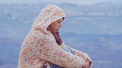 Woman in a hoodie, mountain track, windy day, hair, piercing, close up - stock footage