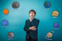 Businessman young teenager boy thinks the planet of the solar sy Kuvituskuvat