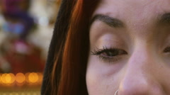 Girl in tears, alone, closeup on her eyes, piercing, nose - stock footage