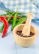 Black pepper in wooden bowl and chili pepper Stock Photos