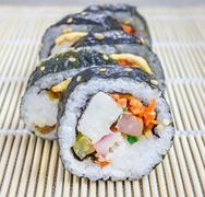 Kimbap on the bamboo mat closeup (Korean cuisine) - stock photo