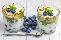 Delicious yogurt dessert with blueberry, kiwi and cereals in the glass Stock Photos