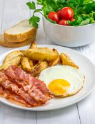 Hearty breakfast with bacon, fried egg, potato and vegetables Stock Photos