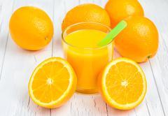 Orange juice and oranges on wooden table - stock photo