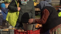 Old lady cheks the potato weight at the market 4K Stock Footage