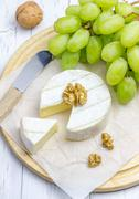 Soft brie cheese with sweet grapes and nuts - stock photo