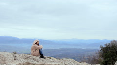Woman in a hoodie, mountain track, windy day, hair, piercing, close up Stock Footage