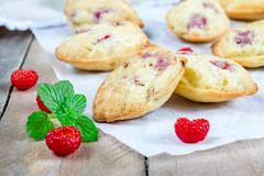 Madeleines cookie with raspberry on parchment paper, closeup - stock photo