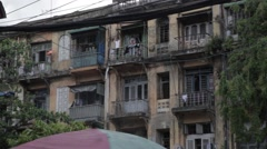 Asian lady  with Laundry on balcony of decrepit building (Yangon/Burma) Stock Footage