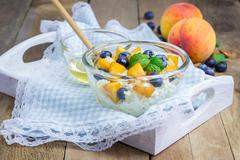 Fresh cottage cheese with peach, blueberry, almonds and honey. Concept of hea Stock Photos