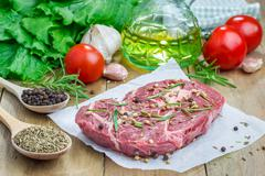 Stock Photo of Raw beef steak with seasoning on a parchment paper
