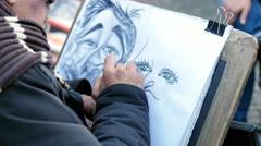 Street artist draws a caricature - stock footage