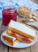 Sandwich with creamy peanut butter and strawberry jam Stock Photos