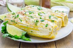 Mexican corn with butter, mayonnaise, parmesan, chili, cilantro, and lime - stock photo