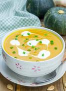 Pumpkin soup with sour cream on a wooden table Stock Photos