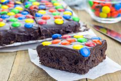 Homemade brownies with chocolate ganache and colorful candies Stock Photos