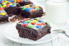 Homemade brownies with chocolate ganache and colorful candies - stock photo