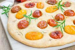 Focaccia with cherry tomatoes and rosemary - stock photo