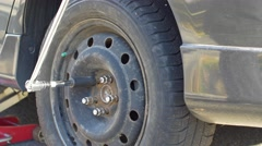 Man tightens wheel nuts on car with breaker bar Stock Footage