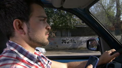 White guy driving a car sends text messages with his mobile Stock Footage