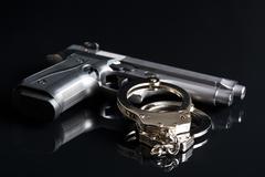 handcuffs and handgun - stock photo