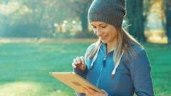 Young adult woman using tablet pc outdoors and looking at camera against the Stock Footage
