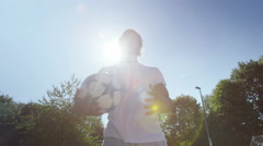 4K Portrait of young man holding a soccer ball at the skate park - stock footage