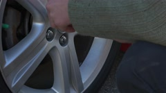Unscrewing car wheel nuts up close Stock Footage