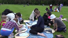 Stock Video Footage of Family construct handmade kites on park meadow. 4K