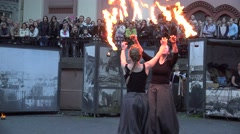 Two women with burning torches perform fire juggle show. 4K Stock Footage