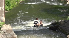 Two young girls wade to overcome wildwater river cascade. 4K - stock footage