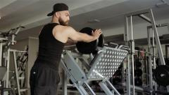 Man workout with simulator leg press in the gym Stock Footage