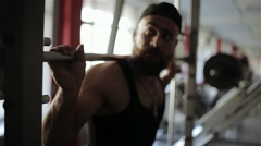 Man puts the ring on the barbell in the gym - stock footage