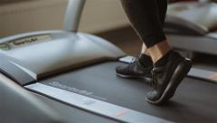 Man comes to the running machine in the gym Stock Footage