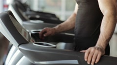 Man chooses a program on a running machine in the gym Stock Footage