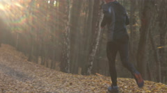 A young man excercising, running on the forest path, sunflare in the shot - stock footage