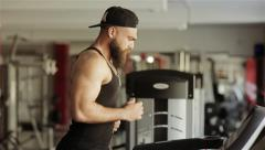 A man runs on a treadmill in the gym Stock Footage