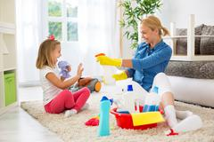 Mother and little girl cleaning house and playing Stock Photos