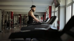A man runs on a running machine in the gym Stock Footage